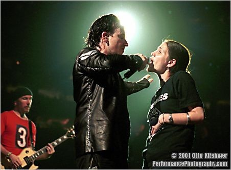 Live concert photo of The Edge, Bono and fan